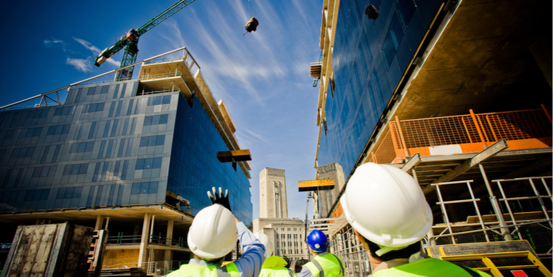 Three mens in high viz jackets and hard hats on a construction site, looking up and pointing towards a crane that's in operation and working on the developments in the background.