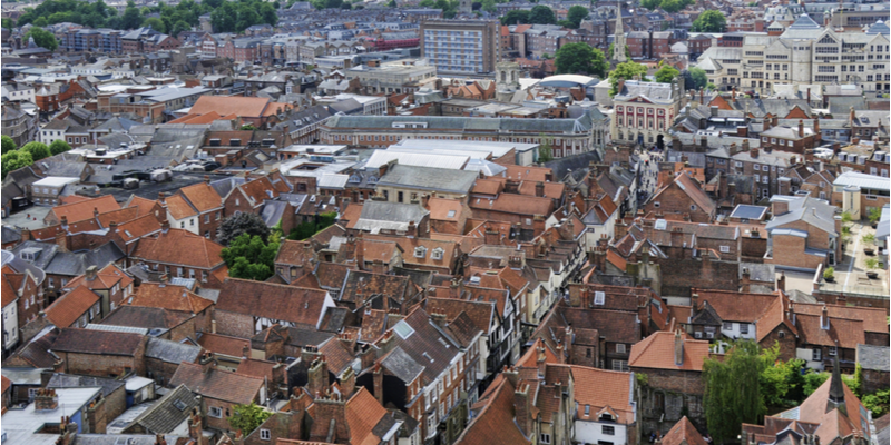 An aerial image looking over the rooftops of buildings in York city centre, taken from the top of York Minster