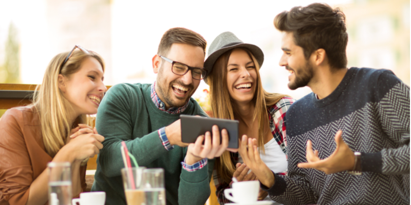 A group of young people engaged in conversation, laughing and smiling whilst catching up in a coffee shop. One man shows the rest of the group something on his mobile device.