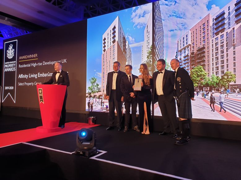 On stage at the 2019/20 UK Property Awards in London. Giles Beswick, Kristen Lee-Mottershead and Gareth Marshall from Select Property Group collecting the award for Residential High-rise Development UK for Affinity Living Embankment West in Manchester, alongside judges and delegates from the UK Property Awards.
