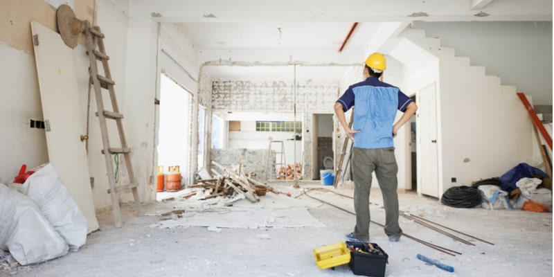 A landlord/property owner standing in their property wearing a hard hat and looking at the renovation work that needs to be done. There are walls that need plastering and painting.
