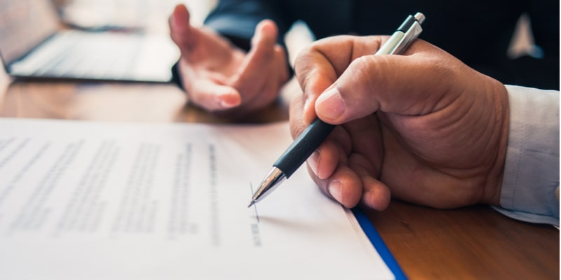 A client and their legal advisor signing a contract. The client's hand is holding a pen which is placed above a signature line on a document, while in the background is the hand of the legal advisor which is gesticulating to suggest the advisor is talking to the client.