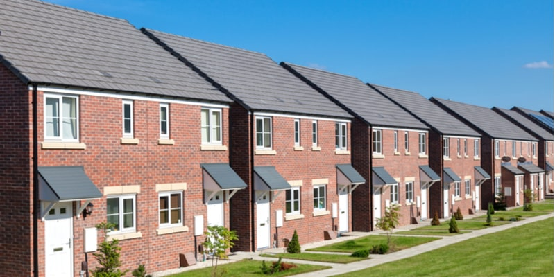 A typical row of newly built homes in the UK. All red brick, with green lawns to the front of each home.