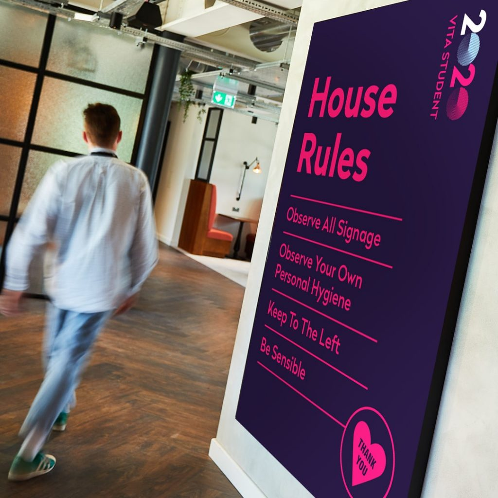 Student walks past a '2020 House Rules' sign inside a Vita Student development.