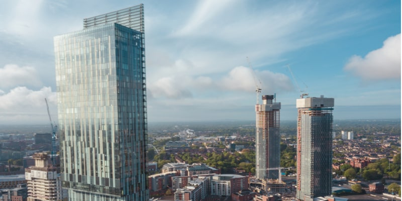 Shot of Manchester city centre's skyline, with Beetham Tower in the foreground and two new in-construction towers in the background