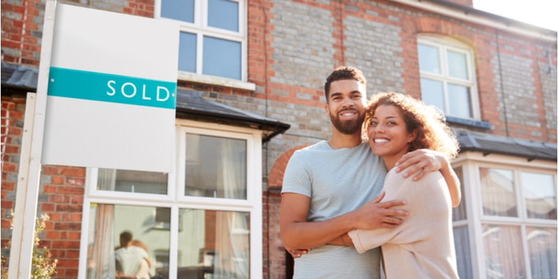Young couple stood outside a residential property with a 'sold' sign in the background. They hug each other and pose, indicating their delighted at buying the property.