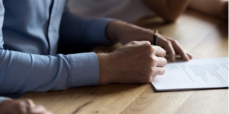 A man sat at a table holding a pen and signing a contract