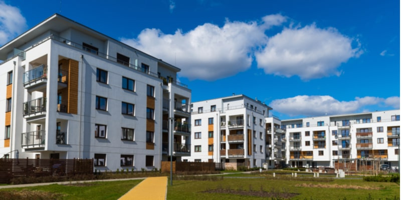 A modern complex of white bricked apartment blocks in the UK, with large communal green space and a blue sky